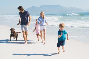 Familie macht Urlaub mit Hund am Strand